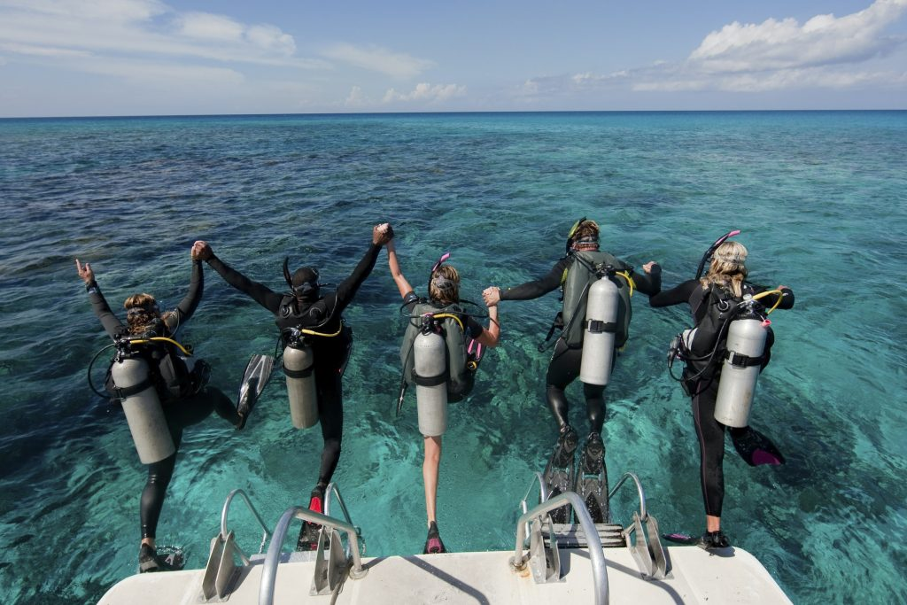 Scuba divers enter water from boat via giant stride entry.,Diving into the water.